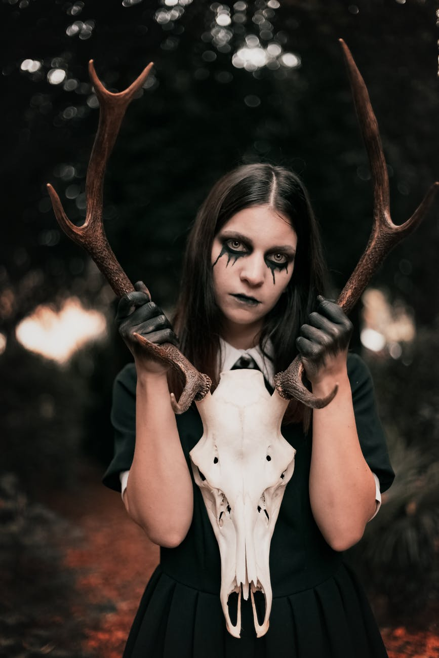 photo of woman holding antler